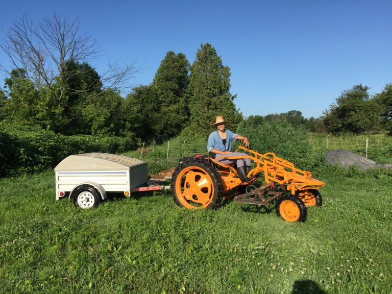 photo of person driving electric tractor with trailer