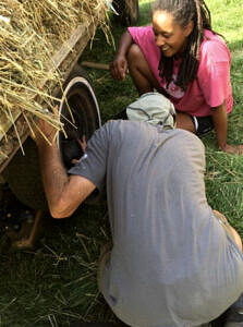 Two farm workers maintaining farm trailer